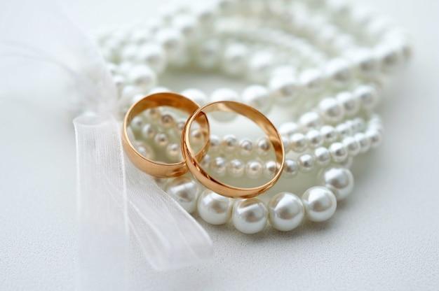 Fedi nuziali e bracciale di perle su sfondo bianco.