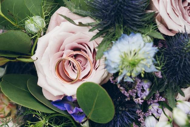 Fedi nuziali su una rosa nel mazzo della sposa