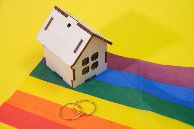 Fedi nuziali e una piccola casa in legno sulla bandiera lgbt, sfondo giallo, luogo di copia, vita familiare di famiglie samesex in un concetto di casa privata