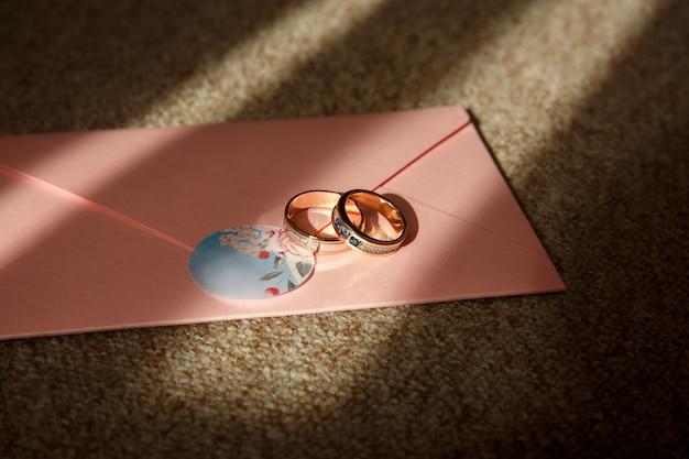 Fedi nuziali con la pietra blu sull'invito di nozze rosa