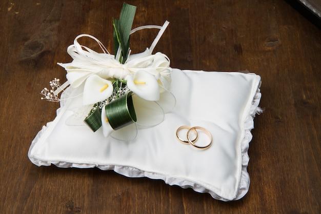 Fedi nuziali con bouquet di calla sulla tavola di legno