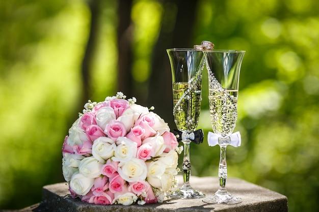 Fedi nuziali con rose e bicchieri di champagne da vicino