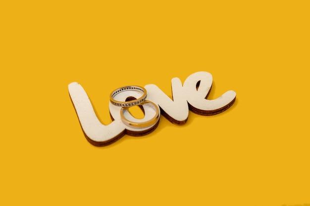 Fedi nuziali con la parola in legno amore su sfondo giallo. concetto di san valentino.