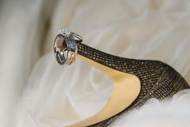 Fedi nuziali per scarpe da donna primo piano delle fedi nuziali sulle scarpe della sposa