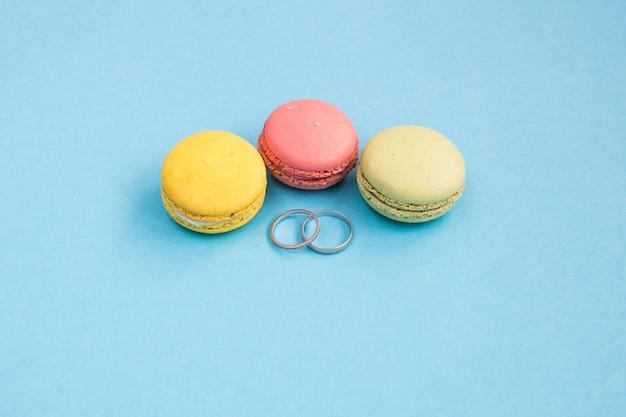 Fedi nuziali sui macarons o sugli amaretti gialli, verdi e rosa sulla vista superiore del fondo del turchese. macaron dall'alto, colori pastello. concetto di matrimonio