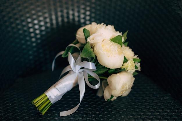 Matrimonio di rose e peonie su una sedia di vimini matrimonio