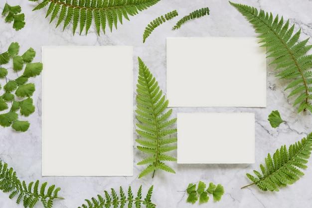 Set di cartoleria per matrimoni e buste decorate con foglie di felce vista dall'alto sul tavolo di marmo. scena di mock-up tropicale con carta di carta bianca distesa piatta