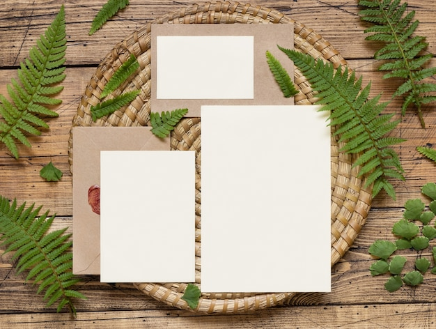 Set di cancelleria per matrimoni di carte e buste decorate con foglie di felce vista dall'alto su un tavolo di legno. scena di mock-up tropicale con carta di carta bianca distesa piatta