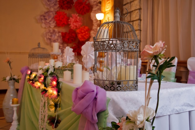 Decorazioni per la tavola di nozze nel ristorante sullo sfondo degli interni. decorazioni floreali da tavola per feste e cene. serve per vacanze, eventi, feste o ricevimenti all'aperto. spazio di copyright per il sito