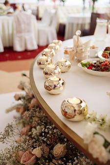 Tavola di nozze decorata con bellissime candele e colori diversi. cibo festivo sul tavolo. banchetto matrimoniale.