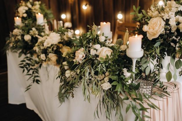 Decorazione della tavola di nozze con fiori sul tavolo, decorazioni per la tavola da pranzo a lume di candela.