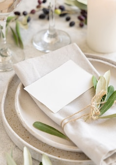 Posto tavola nuziale con cartoncino decorato con rami d'ulivo