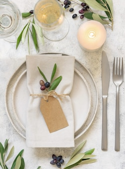 Posto tavola nuziale con segnaposto e piatti in porcellana decorati con rami di ulivo vista dall'alto. elegante modello moderno con carta di carta bianca orizzontale. modello piatto mediterraneo, copia spazio