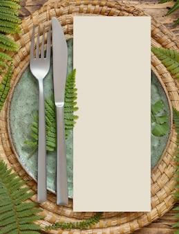 Regolazione della tavola di nozze di piatti, posate e foglie di felce vista dall'alto sul tavolo di legno. scena di mock-up tropicale con carta menu vuota piatta. matrimonio estivo, catering