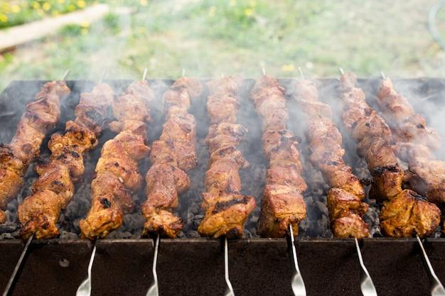 Attività del fine settimana con il concetto di famiglia, gustoso spiedino di barbecue con carne di maiale sul braciere con fumo. foto di alta qualità