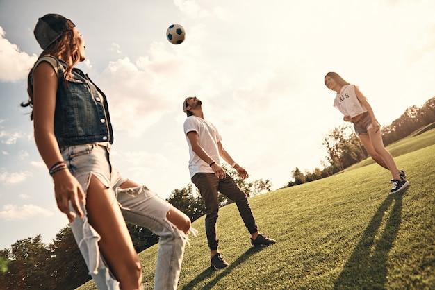 Divertimento del fine settimana! gruppo di giovani sorridenti in abbigliamento casual che giocano a calcio stando in piedi all'aperto