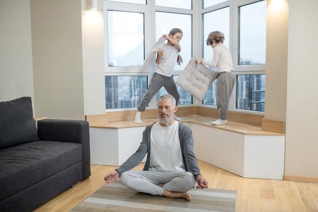 Fine settimana a casa. i fratelli litigano con i cuscini mentre il padre fa yoga