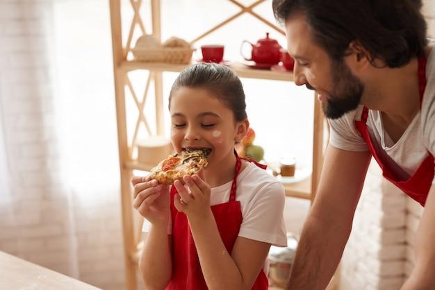 Fine settimana in cucina in grembiule rosso. bambina e papà