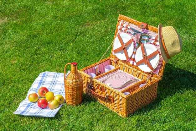 Canestro di paglia di picnic di fine settimana su prato inglese soleggiato verde nel parco