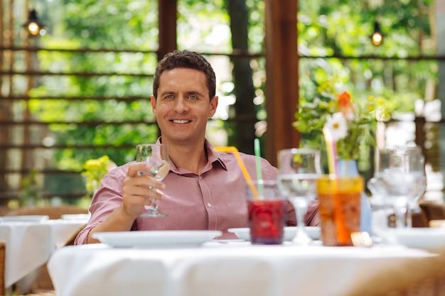 Fine settimana in ristorante. bello imprenditore dagli occhi azzurri sentirsi sollevato mentre trascorre il fine settimana in ristorante