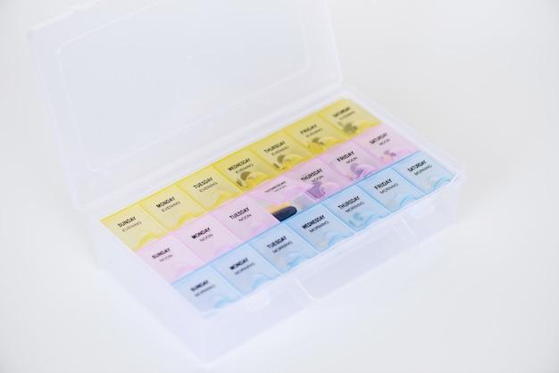 Organizzatore settimanale di pillole di plastica con pillole su sfondo bianco