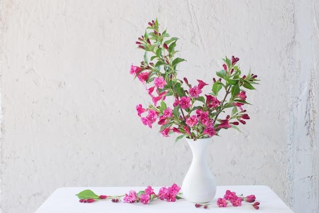 Fiori di weigela in vaso bianco sulla parete bianca