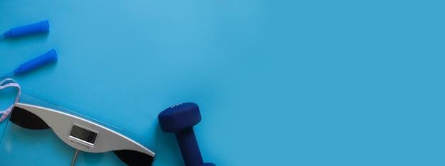 Bilance per saltare la corda e i manubri isolati su uno sfondo blu