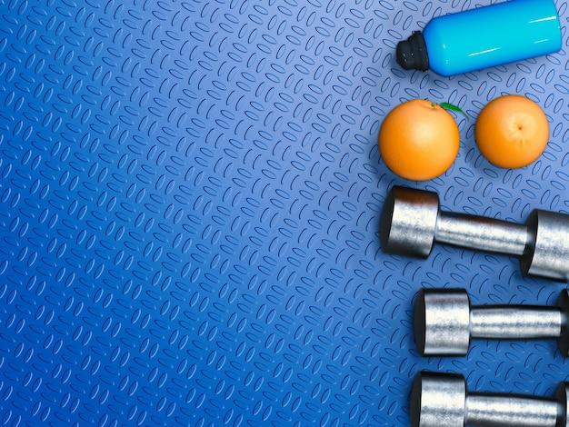 Peso e concetto di dieta con manubri in metallo e arancia