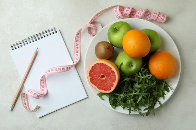 Accessori per la perdita di peso su bianco con texture, vista dall'alto