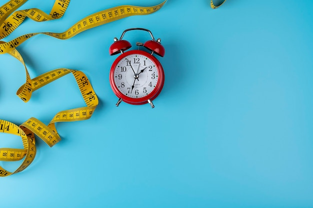Perdita di peso, concetto di dieta, sveglia e metro a nastro, banner web con spazio di copia. vista dall'alto della sveglia rossa e del centimetro giallo sullo sfondo giallo