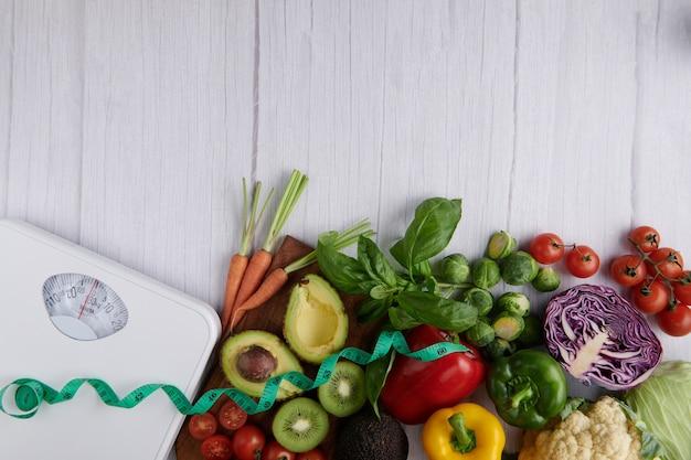 Bilancia dimagrante con diversi tipi di frutta e verdura. vista dall'alto. Foto Premium