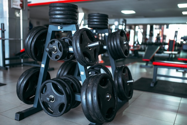Pesi per bar, attrezzature sportive in palestra, interni di fitness club, concetto di bodybuilding