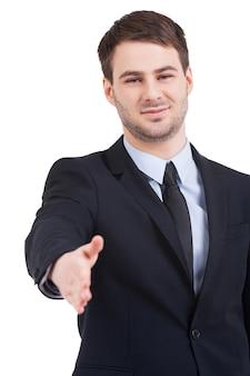 Benvenuto a bordo! fiducioso giovane in abiti da cerimonia che allunga la mano per scuotere mentre sta in piedi isolato su bianco