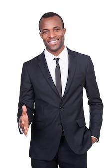 Benvenuto a bordo! bel giovane africano in completo che allunga la mano per scuotere e sorridere mentre si trova isolato su sfondo bianco