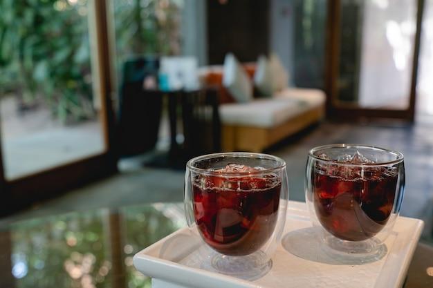 Cocktail di benvenuto rosso mocktail e servito su vassoio di legno bianco.
