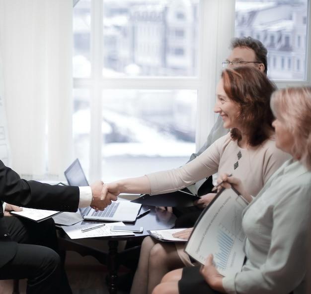 Benvenuto e stretta di mano dei partner commerciali prima dell'incontro in ufficio