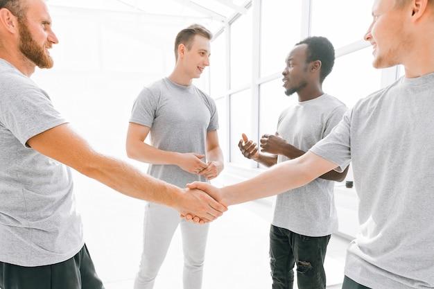 Benvenuta stretta di mano di amici in un ufficio luminoso