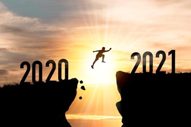 Benvenuto buon natale e felice anno nuovo nel 2021, silhouette man salta dalla scogliera del 2020 alla scogliera del 2021 con cielo nuvoloso e luce solare.