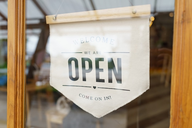 Segno di benvenuto aperto ampio attraverso il vetro della finestra presso la caffetteria. negozio pronto per il servizio,