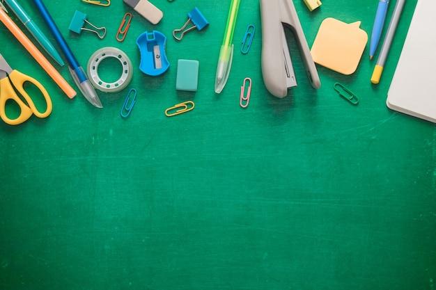Benvenuti a scuola forniture per ufficio su un consiglio scolastico verde varie forniture scolastiche su un malandato verde ...