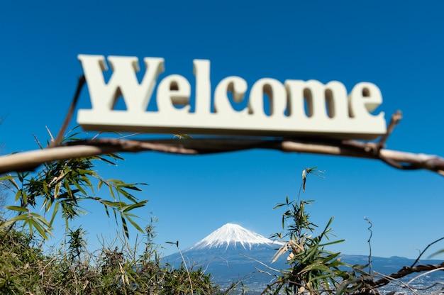 Parola di benvenuto scritta in uno sfondo di legno con vista aerea della città di fuji e monte fuji japan