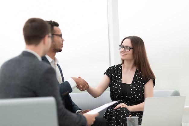 Stretta di mano di benvenuto di un uomo d'affari e di una donna d'affari