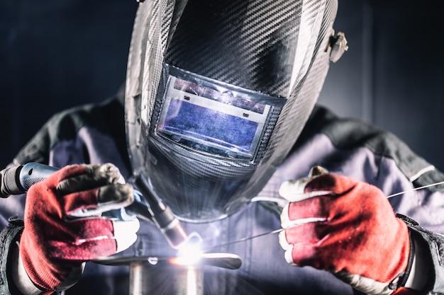 Saldatore operaio industriale saldatura con macchina argon.