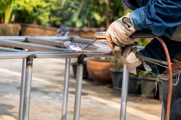 Il saldatore sta saldando il telaio in acciaio. il lavoro e l'industria lavorano duramente.