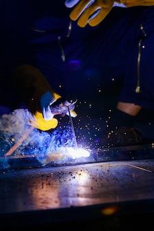 Il saldatore sta saldando l'acciaio insieme per renderlo più forte. il lavoro produce scintille luminose hanno il fumo, l'effetto della luce e il fumo fanno sembrare una bella luce blu. arc è uno specialista che richiede abilità.