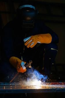 Saldatore seduto in fabbrica che salda insieme l'acciaio per renderlo più forte. il lavoro produce scintille luminose hanno il fumo, l'effetto della luce e il fumo fanno sembrare una bella luce viola.
