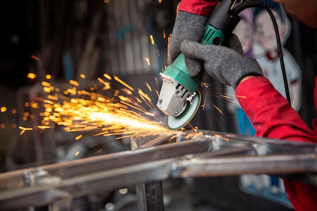 Il saldatore ha usato la mola su acciaio in fabbrica con scintille, processo di saldatura presso l'officina industriale, mani con strumento nel telaio. Foto Premium