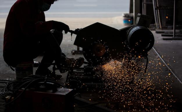 Il saldatore ha usato la mola su acciaio in fabbrica con scintille, processo di saldatura presso l'officina industriale, mani con strumento nel telaio.