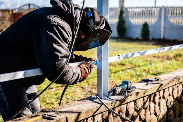 Un saldatore che indossa un casco di sicurezza e guanti sta saldando una recinzione metallica