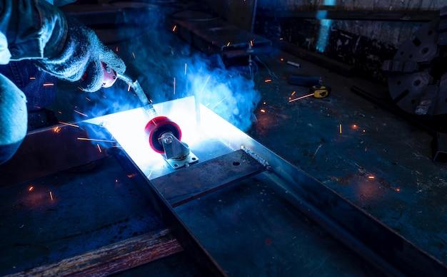 Saldatore di metallo di saldatura con saldatrice ad arco di argon e ha scintille di saldatura un uomo indossa guanti